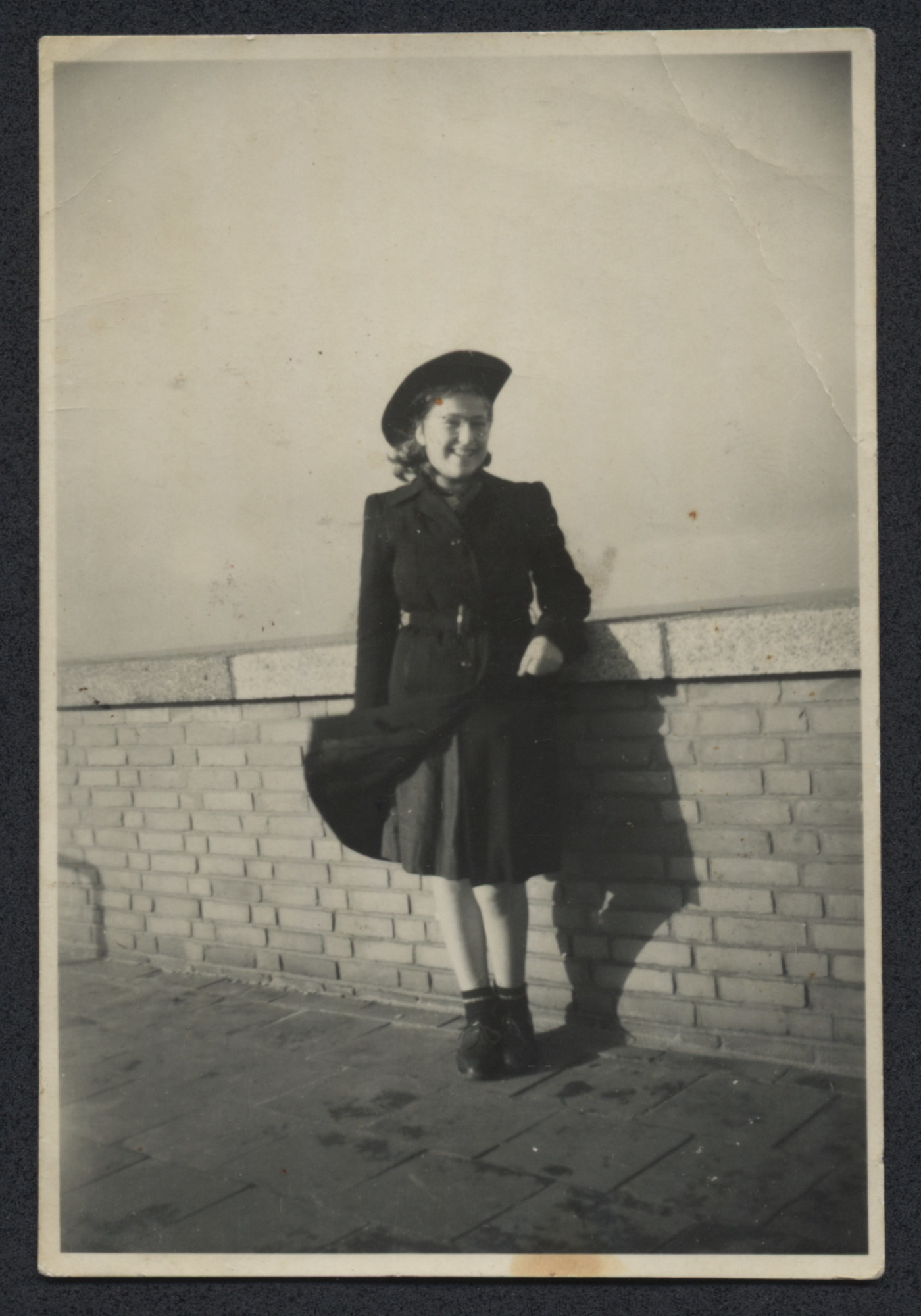 Elly van Leeuwen, poses by a brick wall immediately after the war.