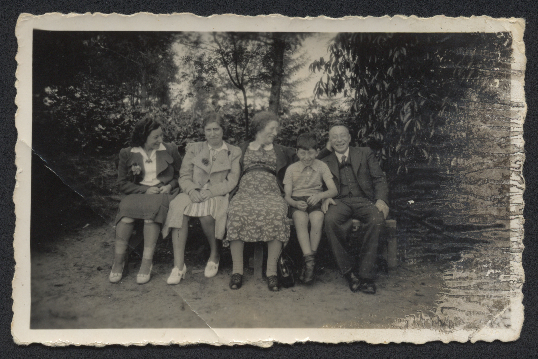 """A Jewish family sits on a park bench before the war.  Pictured are Engeline [?], [unknown], Froukje, Louis, and Siemon Moses.  The inscription on the back reads, """"Ind Leusden Augustus 1939 vacantie.""""  (In Leusden, August 1939, vacation.)"""
