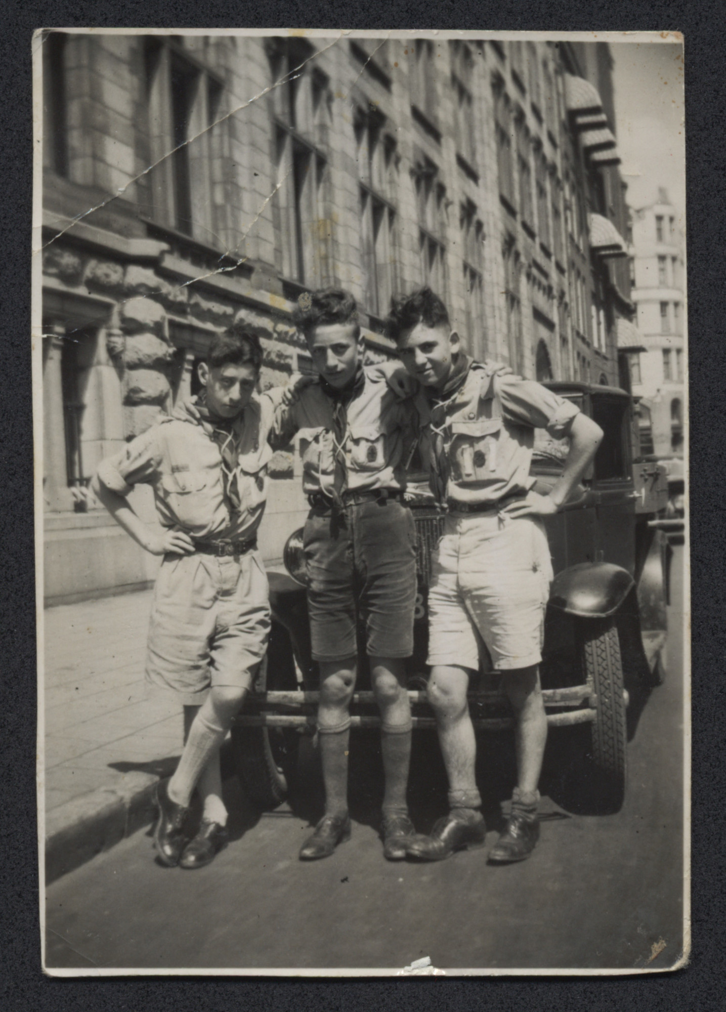 "Three boys in scouting uniforms pose on a city street.  Pictured on the right is Louis Moses.  The inscription on the back reads, ""Voor mama, Trektocht n. Wieringermeer 1947.  Amsterdam."" (For Mama, Hiking at  Wieringermeer 1947.  Amsterdam.)"