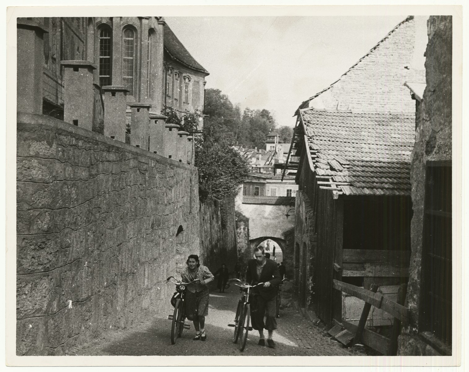 "Two women walk their bicycles down a street in Steyr, Austria.    The handwritten caption on the back of the photograph reads: ""Street in Steyr, Austria."""