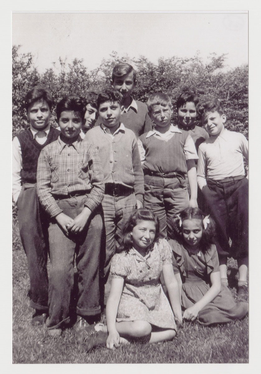 Group portrait of the Ft. Ontario refugee children of the fourth grade class at the Campus School of Oswego State Teachers College, 1944.  Henry Brecher is standing on the far left.  Walter Greenberg is in the center, and Ivo Hirschler is to his right.