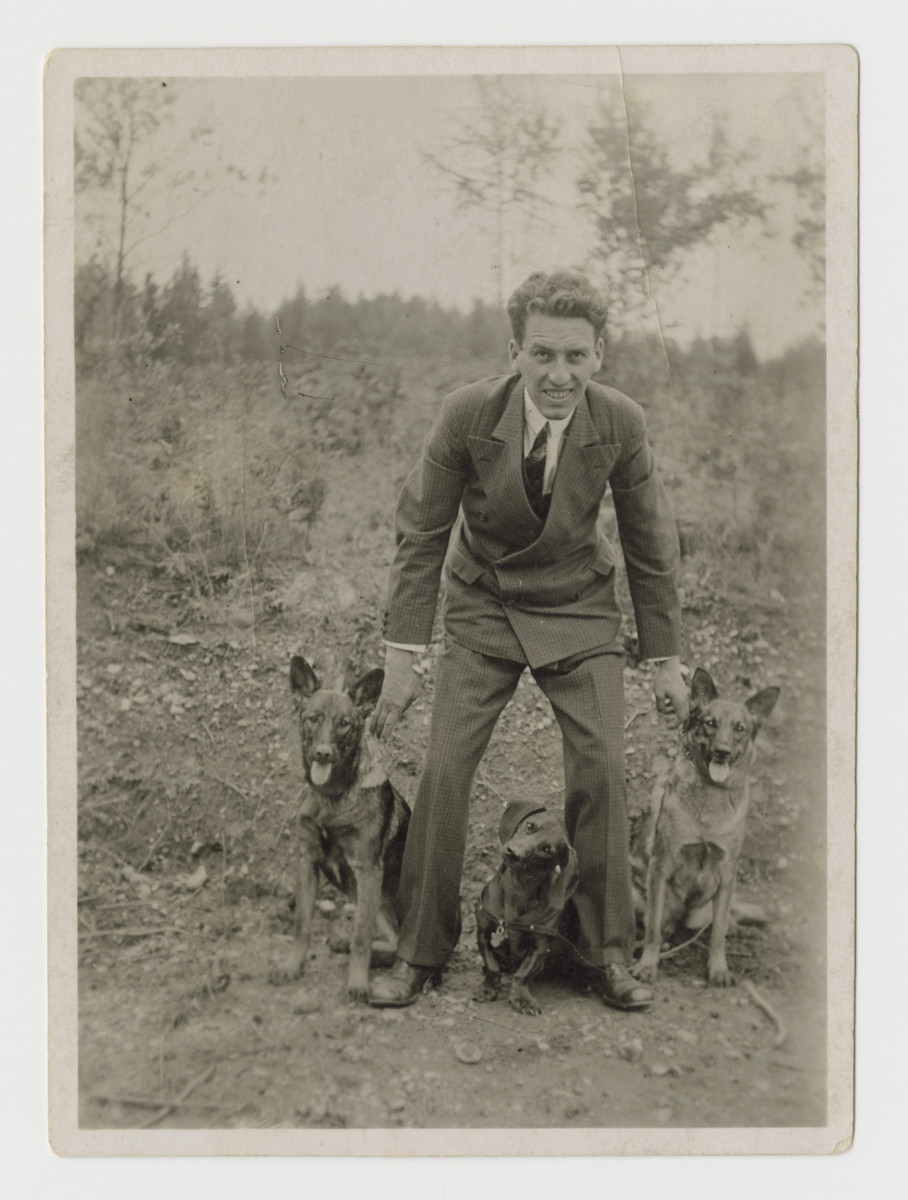 Ernst Brecher poses outside with three dogs in Graz, in the mid-1930s..