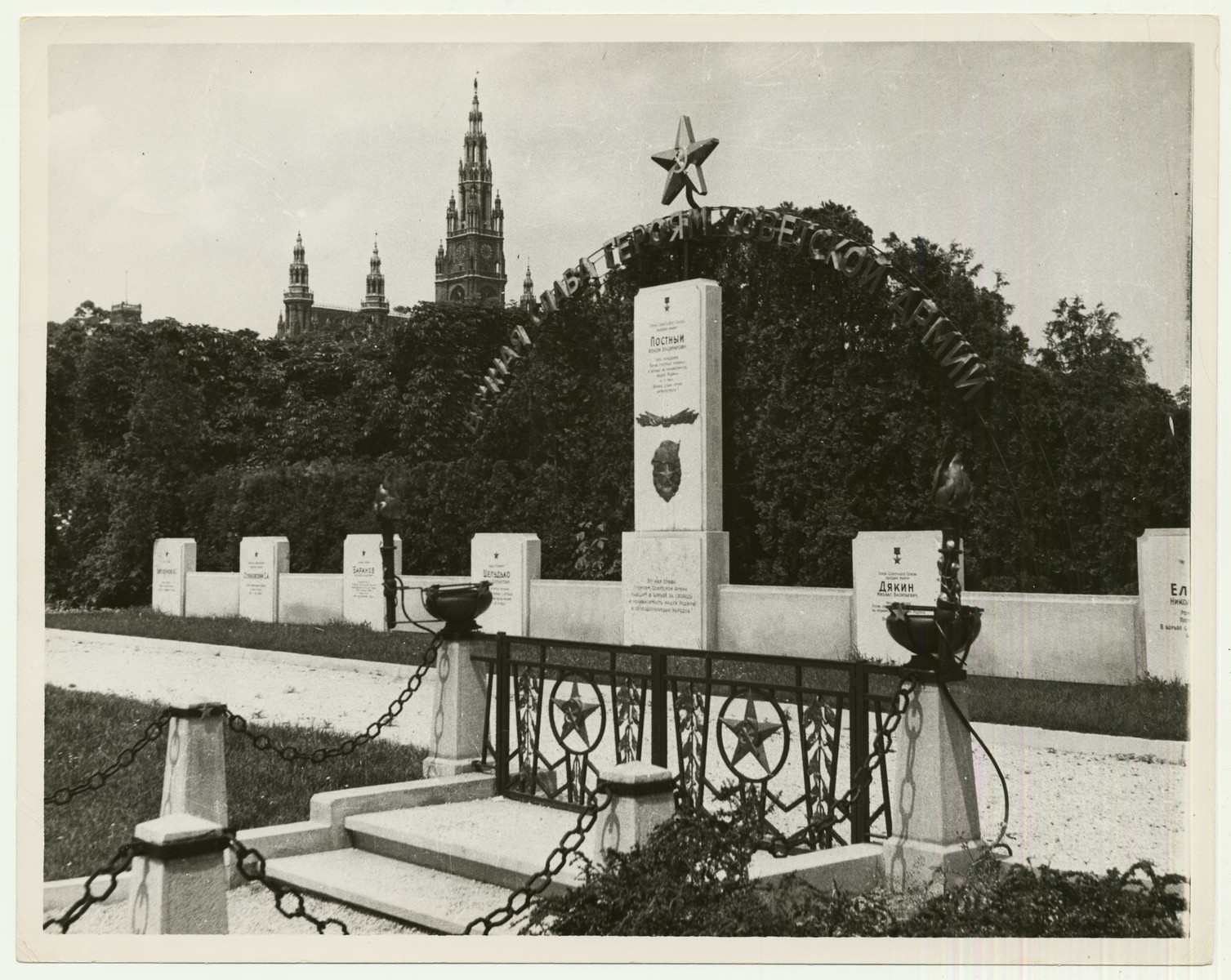 """View of the markers for Russian graves in Vienna, Austria outside City Hall.  The handwritten caption on the back of the photograph reads: """"Russian graves in Vienna, City Hall in background."""""""