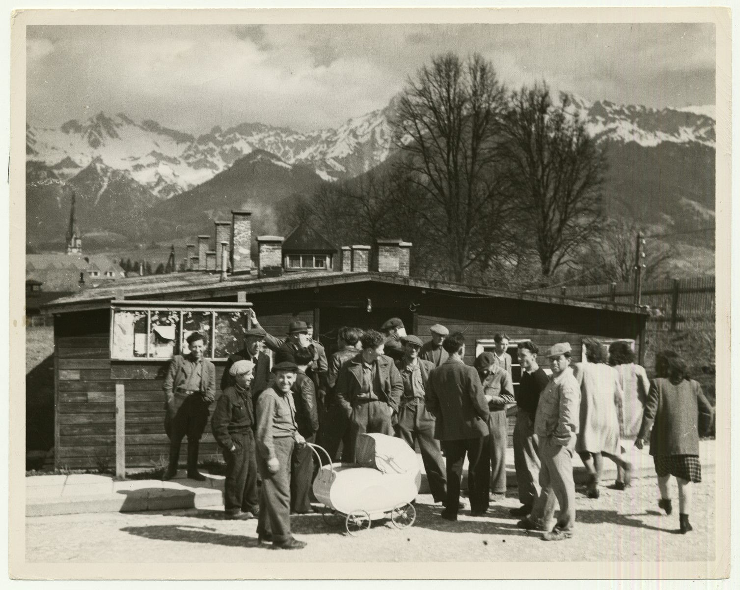 """Holocaust survivors gather in a displaced persons camp in Admont, Austria  The Admont DP camp, located in the British zone of Austria, was one of the largest, housing about 2000 Jews.  The camp was closed in 1948.  The handwritten caption on the back of the photograph reads: """"A DP Camp in Admont, Austria."""""""