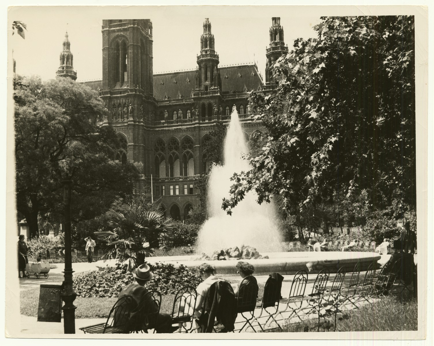 "Photograph of the restored Rathhauspark (City Hall Park) in Vienna, Austria. City Hall appears in the background.  The handwritten caption on the back of the photograph reads: ""Restaurated [sic] ""Rauthauspark"" in Vienna.  City Hall in background."""