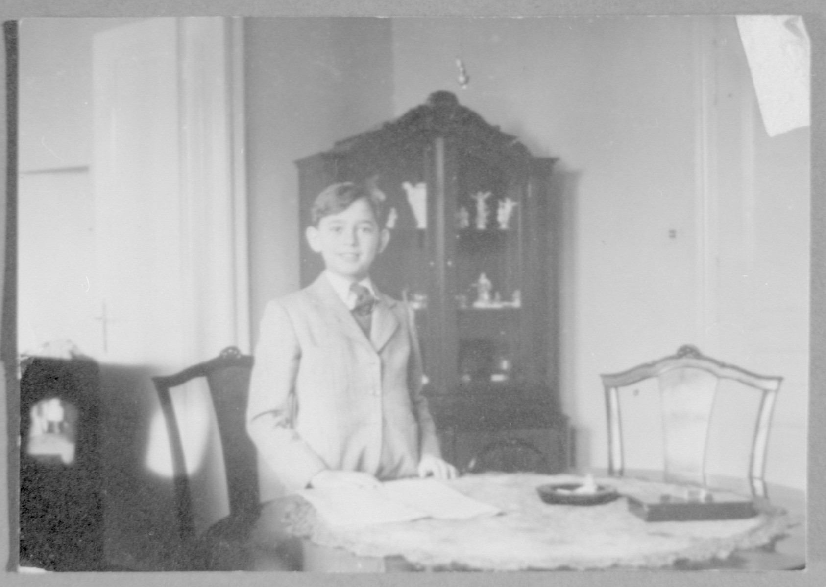 Roman Frister stands by the dining room table in his home.