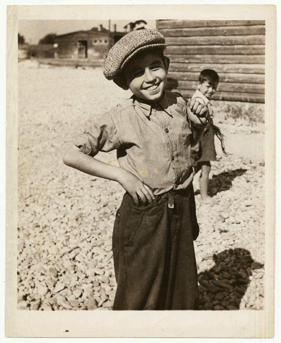 "A boy sports a new cap in a displaced persons camp in Austria.  The typed caption accompanying the photograph reads: ""This smiling lad, of the 38,000 surviving Jewish children in Austria and Germany under the protective care of the Joint Distribution Committee, is sporting a new cap-- manufactured in a JDC-established capmakers' shop under its work project system.  In addition to those articles of clothing manufactured in the workshops, JDC last year shipped almost 34,000,000 pounds of life-sustaining commodities to distressed Jews in Austria and Germany.  JDC, major American agency providing Europe's Jewish men, women and children with extensive supplementary food, clothing, medical care, welfare, rehabilitative and emigration assistance, receives its funds from the $250,000,000 campaign of the United Jewish Appeal."""