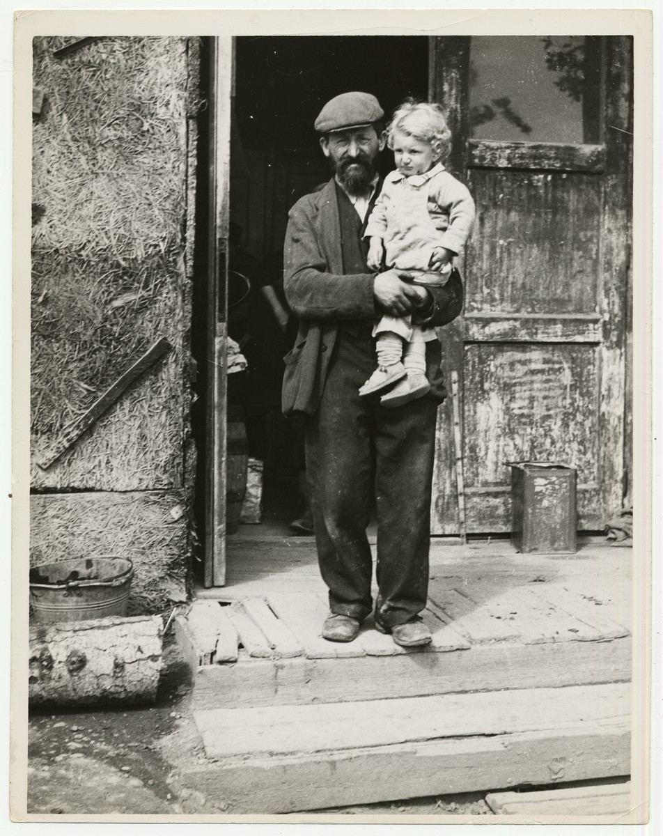 "A man holds his young child in the entrance to a building in a displaced persons camp in Austria  Handwritten caption on the back of the photograph reads: ""In a Displaced persons Camp in Austria."""