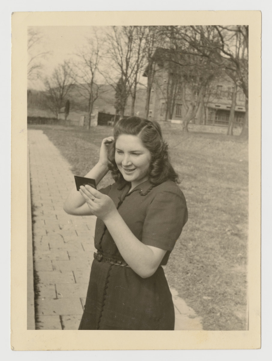 Lenka Gruenberg fixes her hair in the mirror whlile standing outside the Deggendorf displaced persons camp.