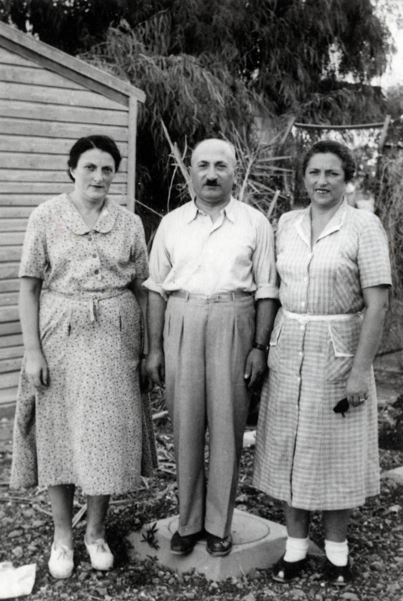 Josef and Yetti Kollenberg (right) stand outside a house next to Yetti's sister, Dora.