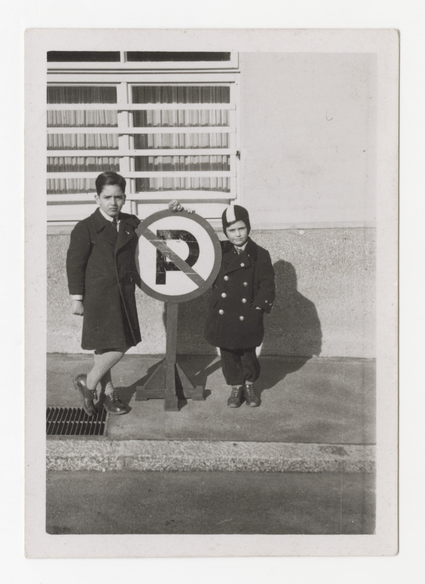 Heinz Brecher and his older cousin Robert Mayer stand next to a no parking sign in front of Heinz's apartment building in Graz.