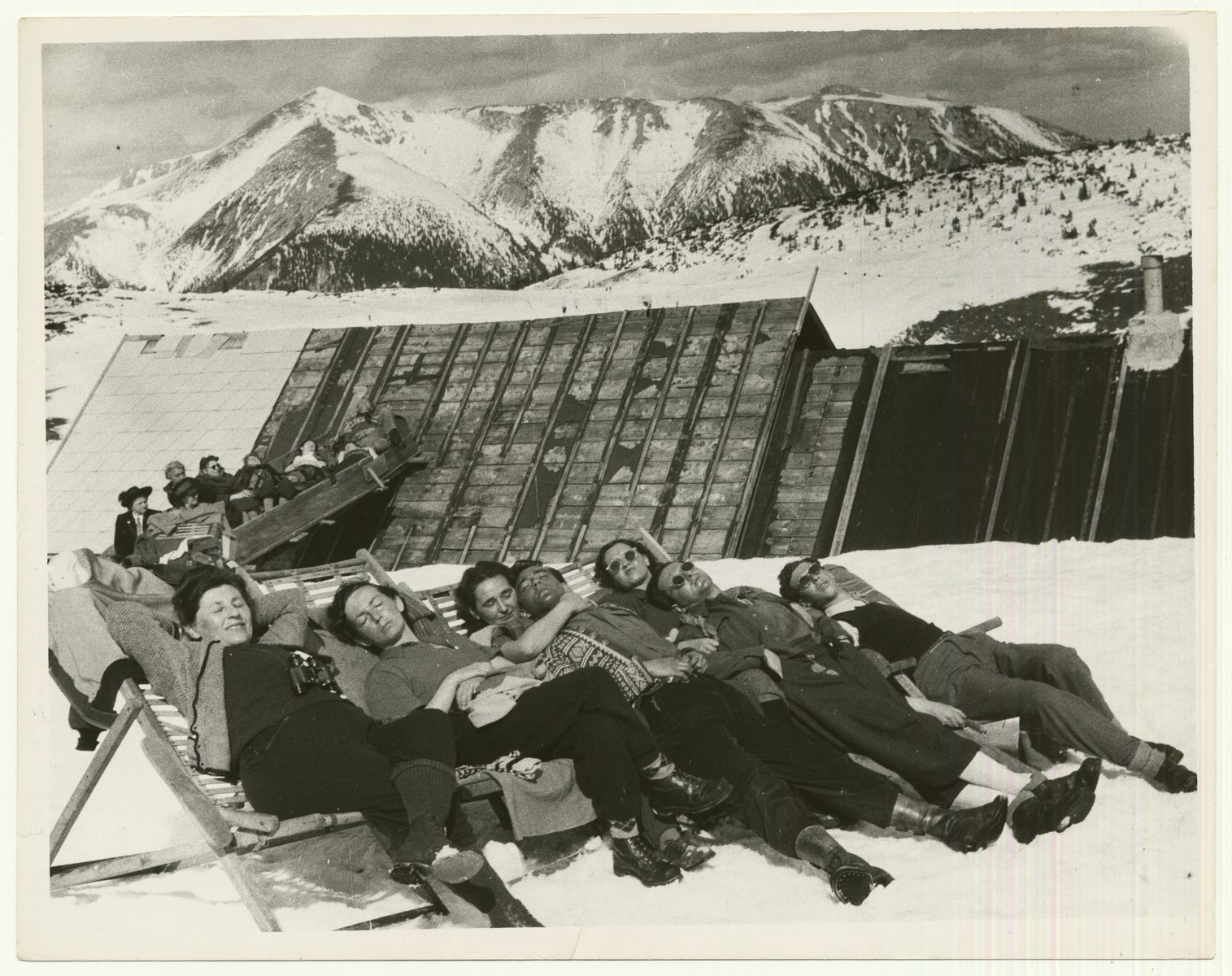 """Women relax in the Austrian Alps  The handwritten caption on the back of the photograph reads: """"Enjoying snow and sun on summit of Rax Alp, Austria.  Snow covered mountain is the Schneeberg."""""""