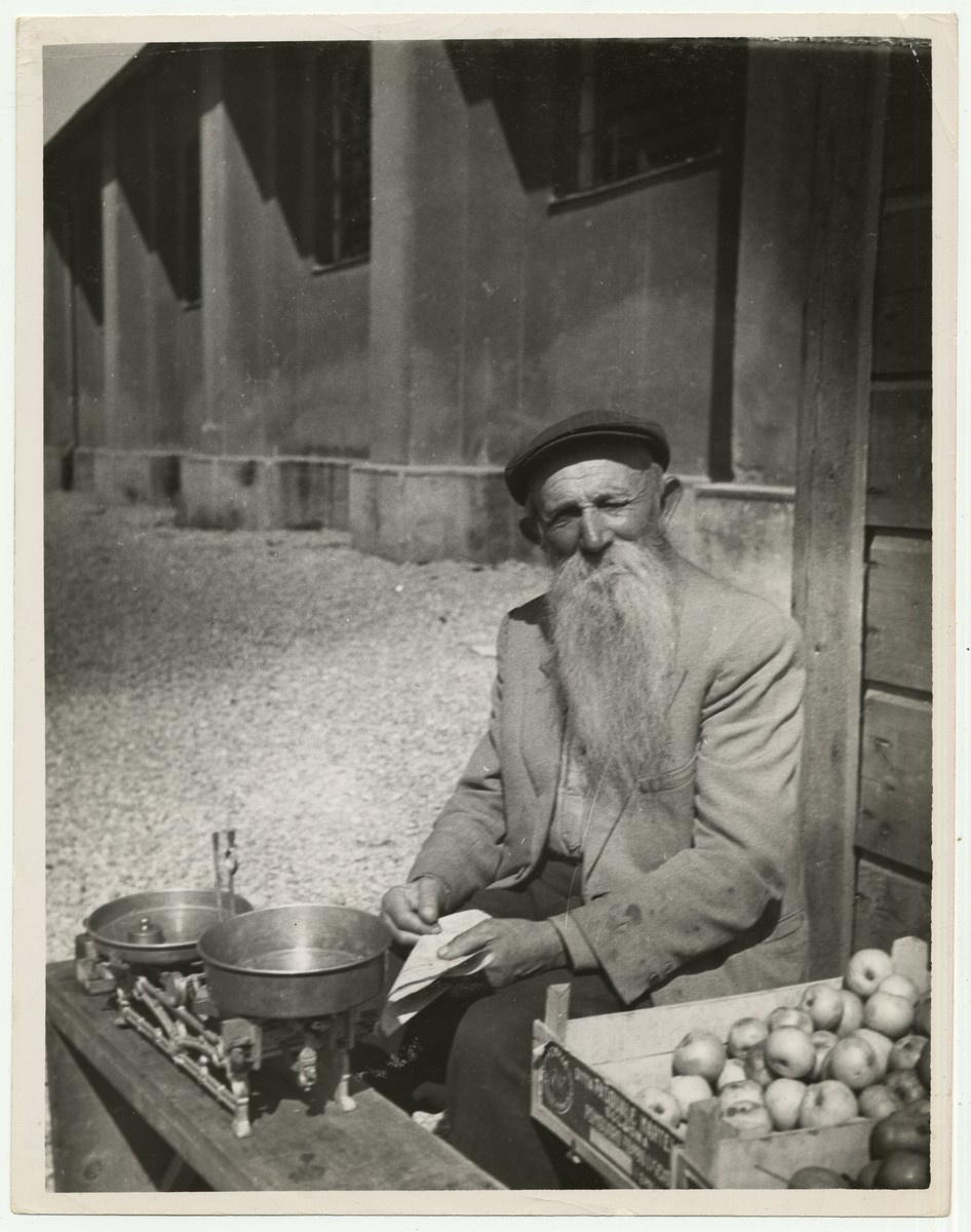 "A Holocaust survivor sellls apples outside an Austrian DP Camp  The handwritten caption on the back of the photograph reads: ""DP, Austrian Camp."""