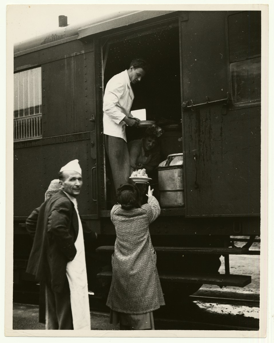 "A woman unloads food supplies from a kitchen wagon in Bremen.  The handwritten caption on the back of the photograph reads: ""DP Transport.  IRO Train to Bremen, Germany.  Kitchen waggon [sic]"""