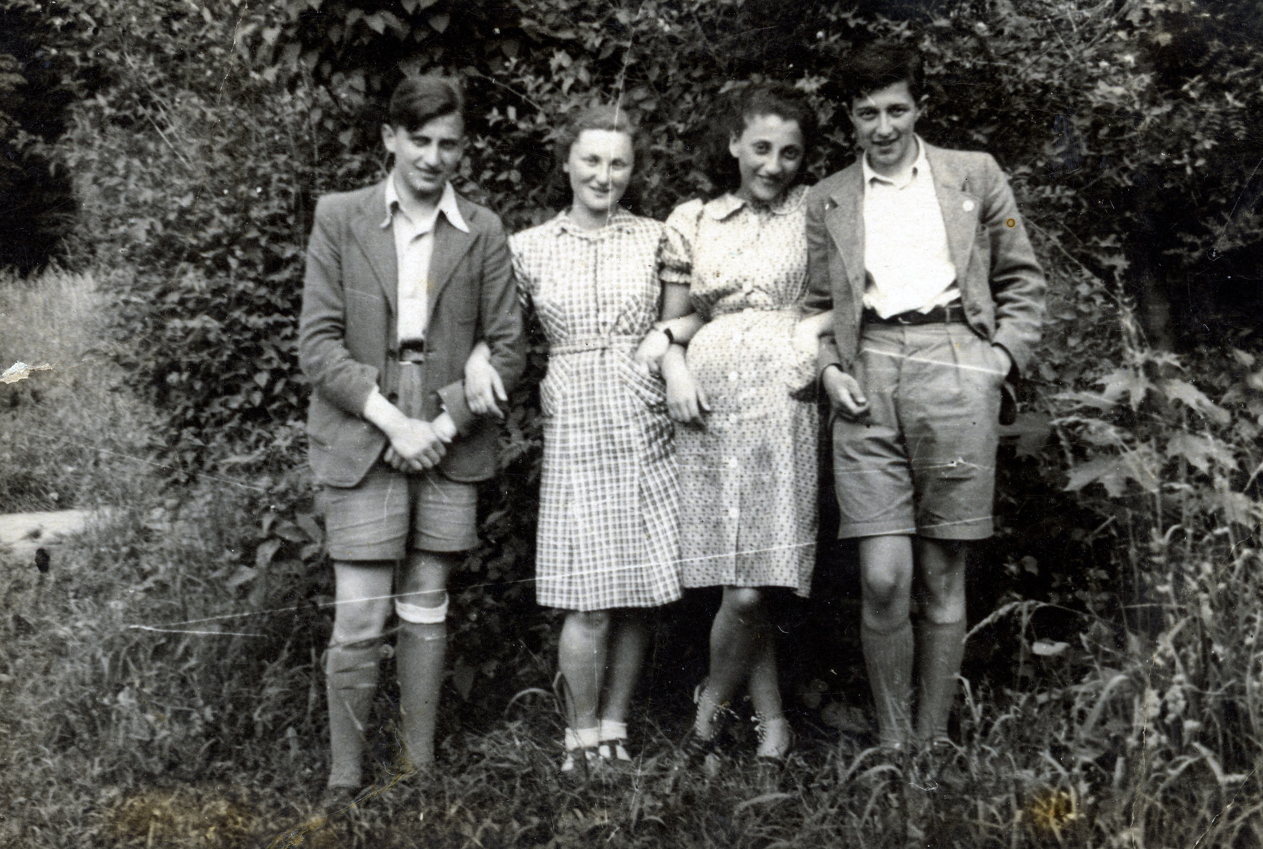 A group of Jewish youth pose in a park during the Soviet occupation of Cernauti/Czernovitz.  Thea Kollenberg (pictured second from the right) with her friends from school (Sheva Hoenig second from the left, Ossie Nagle on the far left, and Kurt Sherf on the far right).