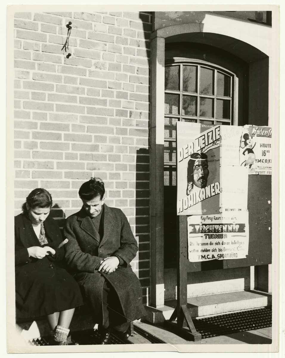 "A man and a woman wait for DP Transport in the International Refugee Organization Center in Camp Grohn in Bremen, Germany.    Camp Grohn was a military base of the U.S. Army after the end of World War II.  It became the largest displaced persons camp, housing as many as 5000 displaced persons prior to their emigrating the the United States or elsewhere.  A handwritten caption on the back of the photograph reads: ""DP Transport.  The last days of waiting.  IRO Center Bremen-Grohn, Germany.  Posters show activities of YMCA in camp."""
