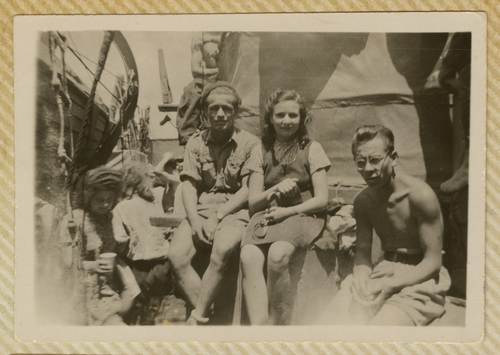 Miriam Ofer and two male companions sit on the deck of the Biriah while en route to Palestine.
