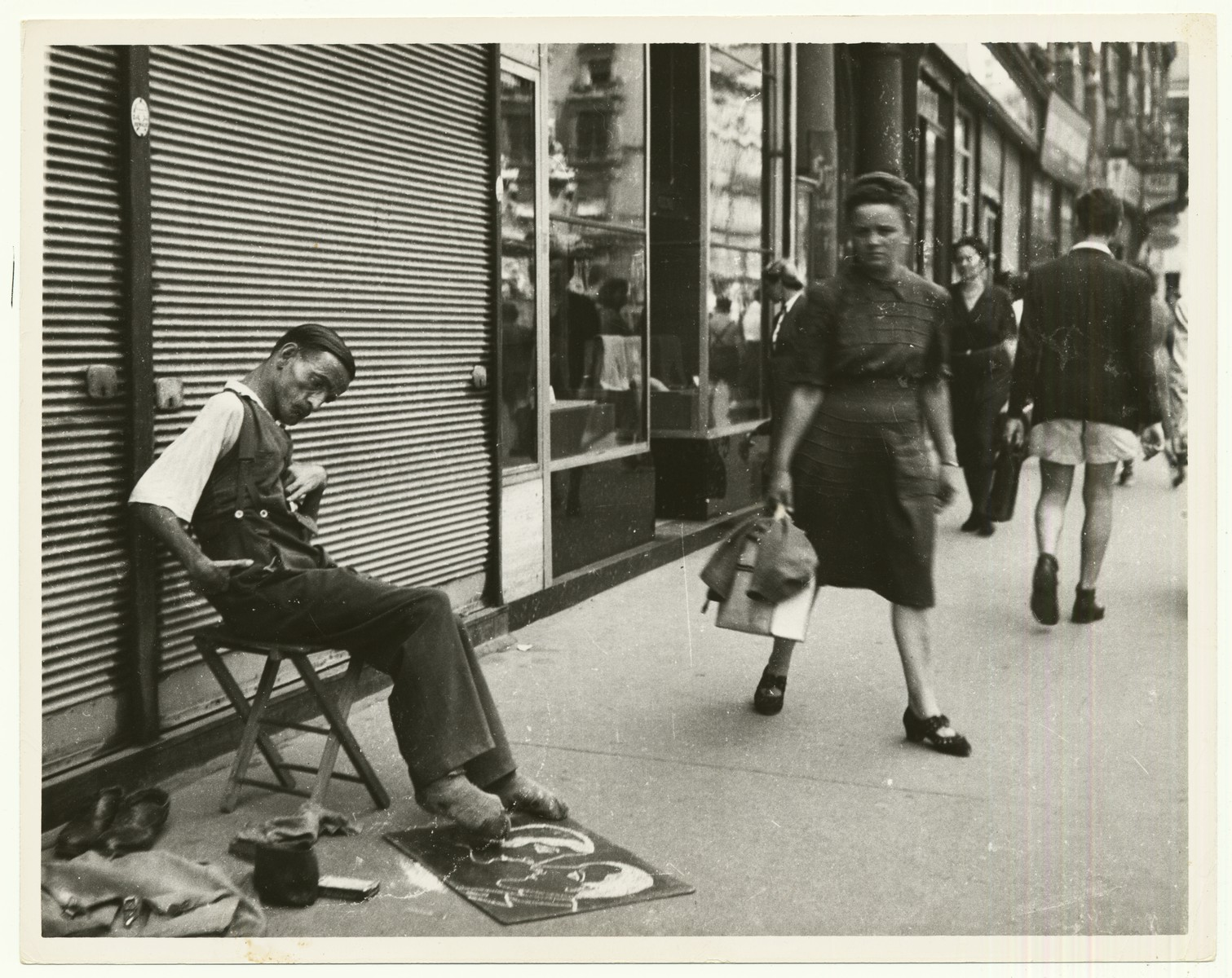"A partly paralyzed beggar sketches with his foot on the Graben in Vienna, Austria  The Graben is one of the most famous streets in Vienna's first district, the city center.  The handwritten caption on the back of the photograph reads: ""Partly paralyzed beggar in Vienna on the Graben, drawing with foot."""