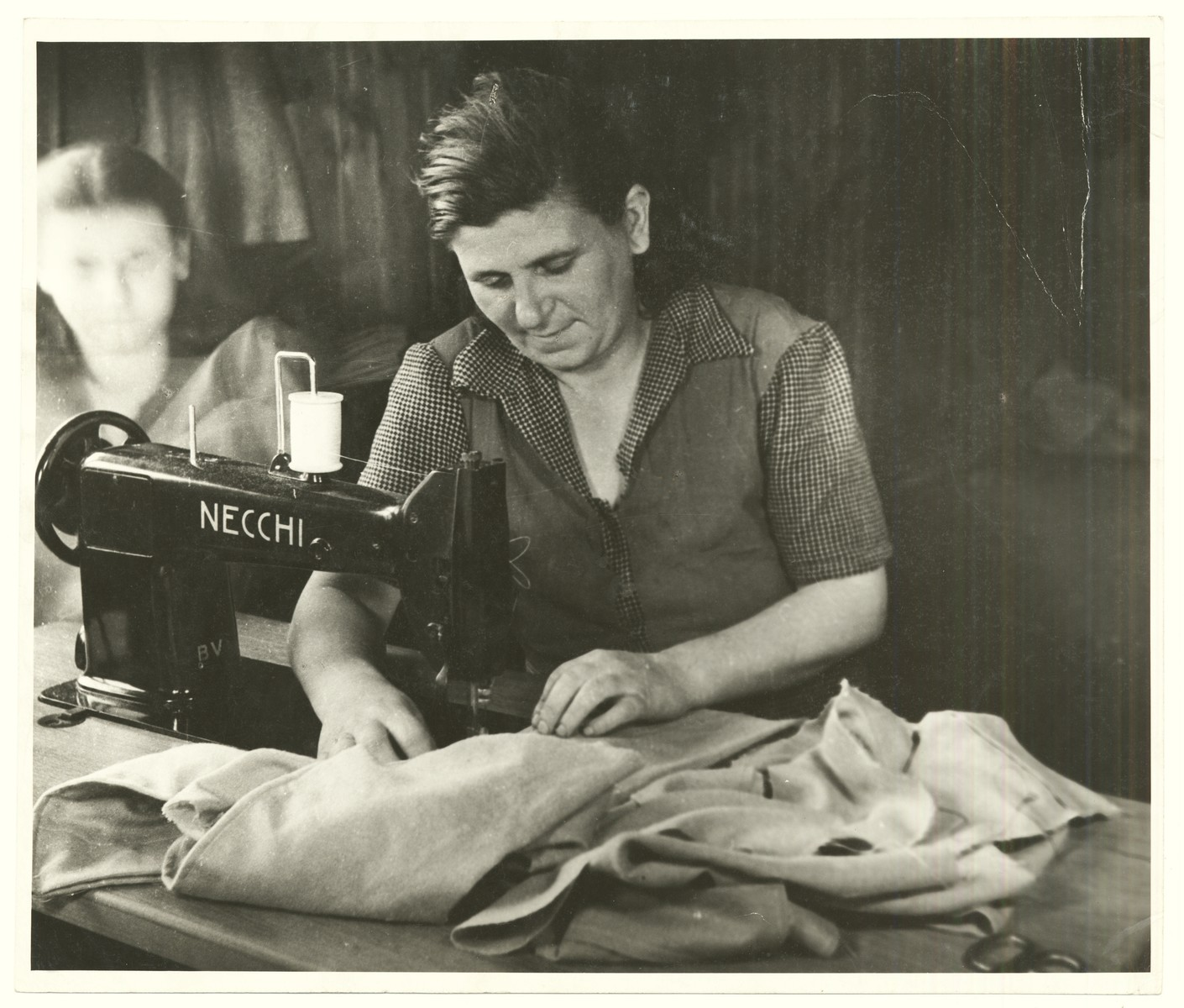 A woman works in a sewing factory in a displaced persons camp, probably in Vienna.