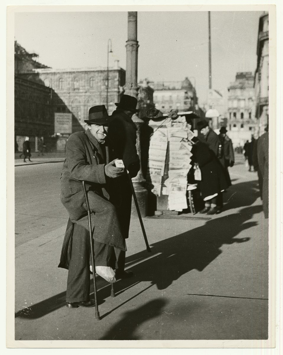 """A man on crutches sells blackmarket cigarettes on the street in Vienna, Austria. The opera house appears in the background.  The handwritten caption on the back of the photograph reads: """"Cigarette Blackmarketeer in Vienna.  Operahouse [sic] in the background."""""""