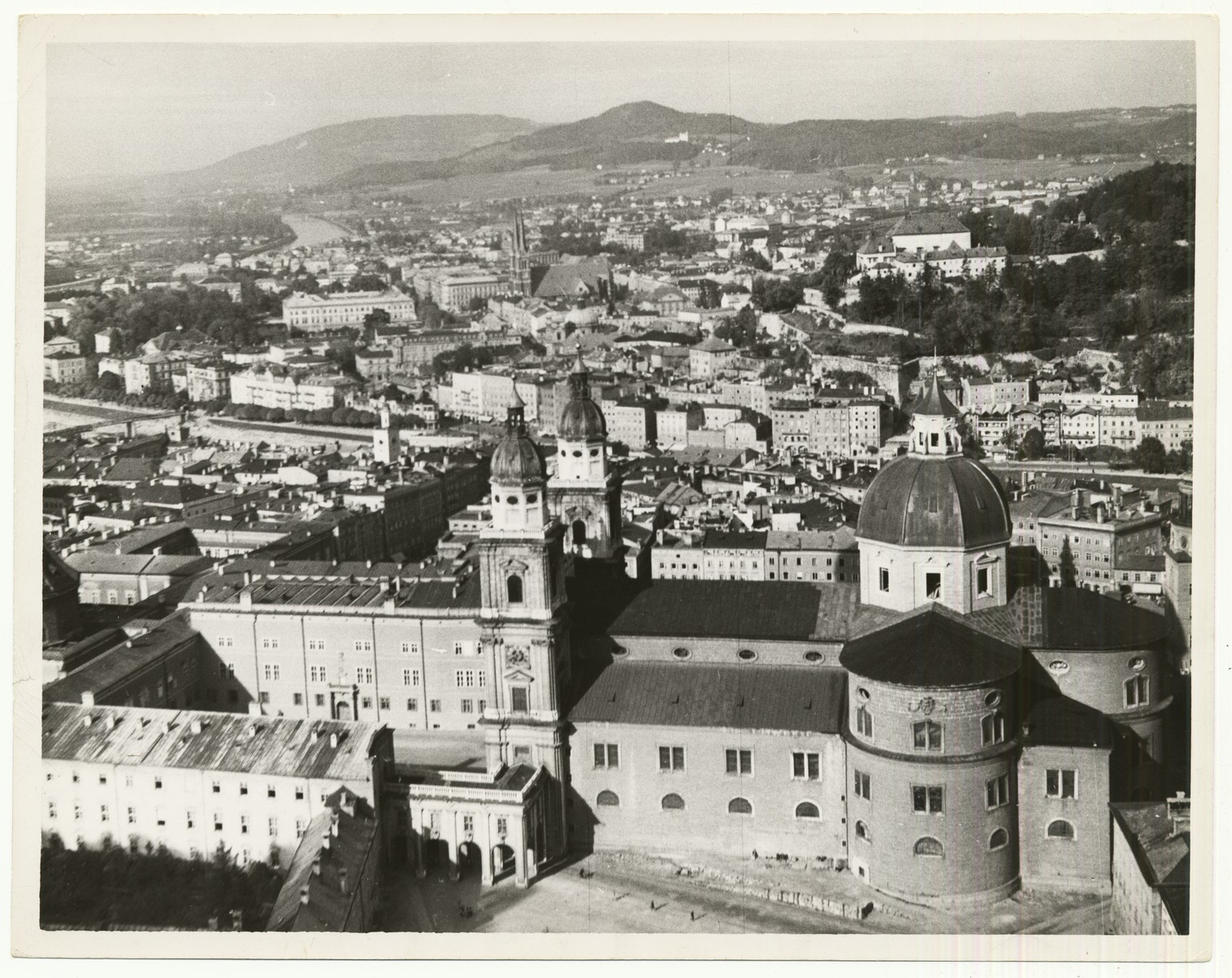 """A view from Hohensalzburg Fortress in Salzburg, Austria.  In the foreground is the Salzburg Cathedral.  The handwritten caption on the back of the photograph reads: """"Salzburg, Austria, view from Fortress Hohensalzburg.  In foreground the Dom (Cathedral), in front of which the """"Everyman"""" (Jedermann) performances during the Salzburg festival take place."""""""