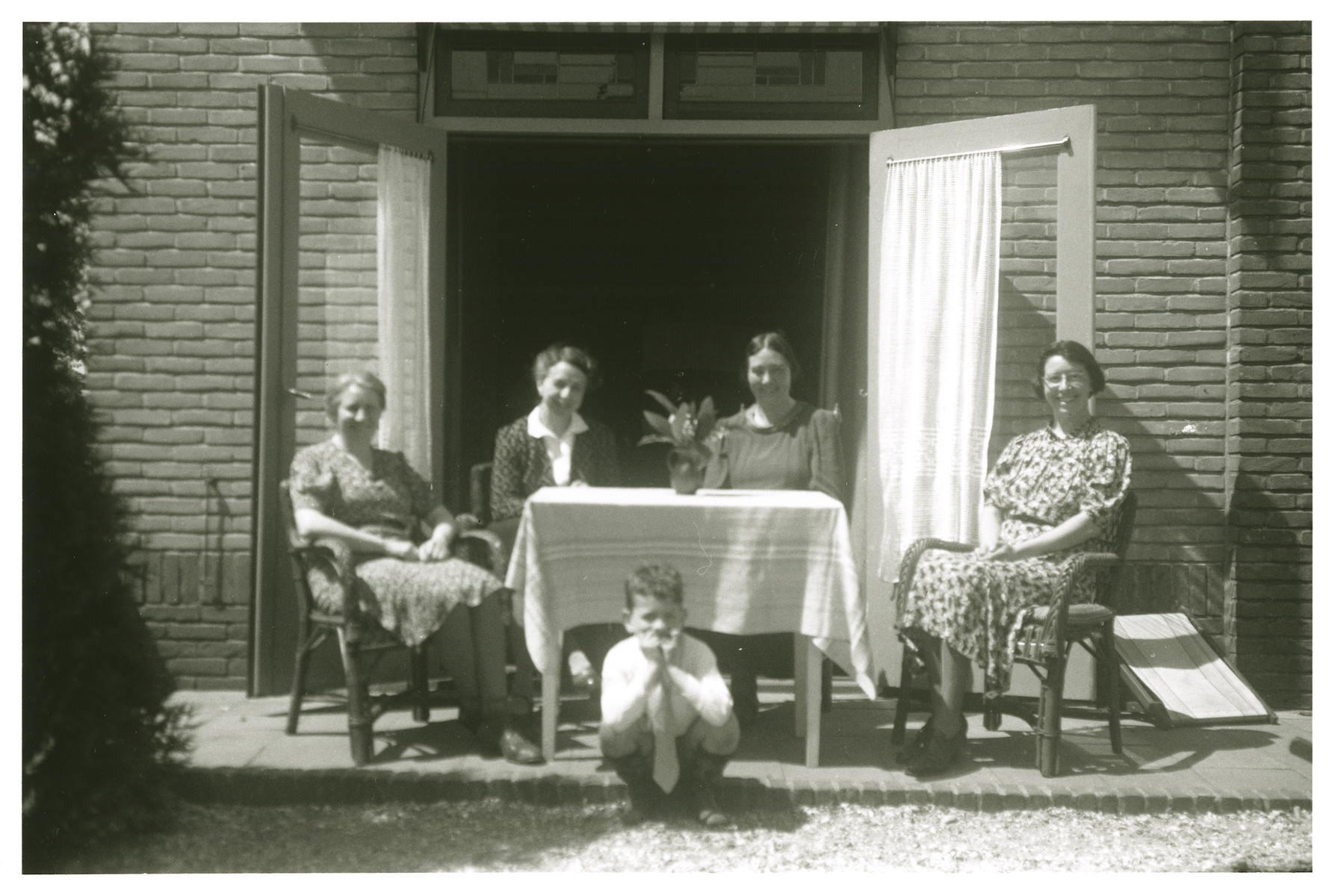 Max Amichai Heppner squats in front of a table where four women sitting [either while in hiding or immediately before].  [His mother is probably on the far right.]