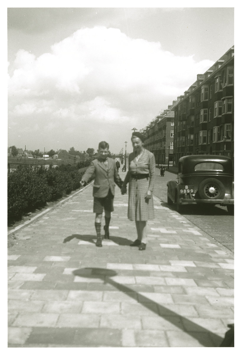 Max Heppner walks down a street in  Amsterdam together with a woman [perhaps his mother] after the war.
