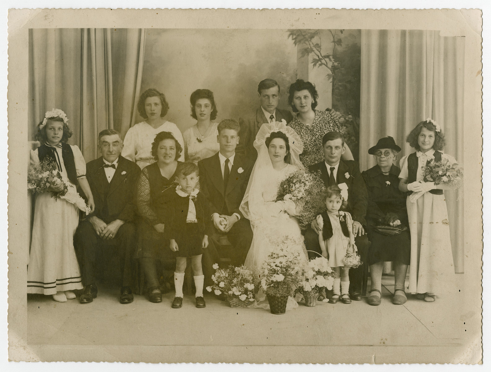 Portrait of the Bocahut family at a wedding celebration (sitting to the groom's right).   Jacques Karpik, who at the time was a child in hiding with this family, appears at the bottom left in front of Suzanne Bocahut.  The little girl is his sister Annette.  Directly behind her is Marcel Bocahut.