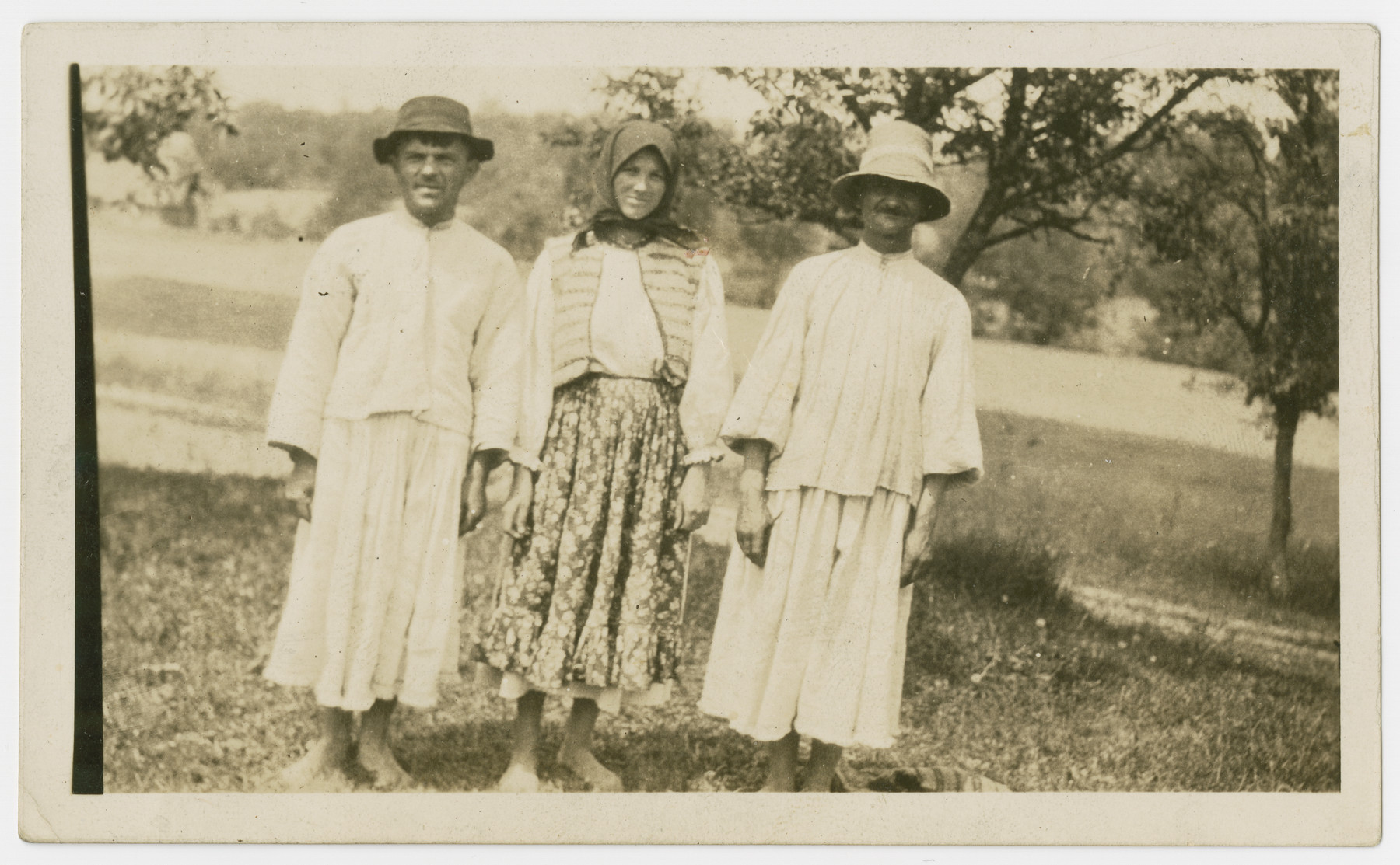 Three family members stand outside to pose for a portrait.