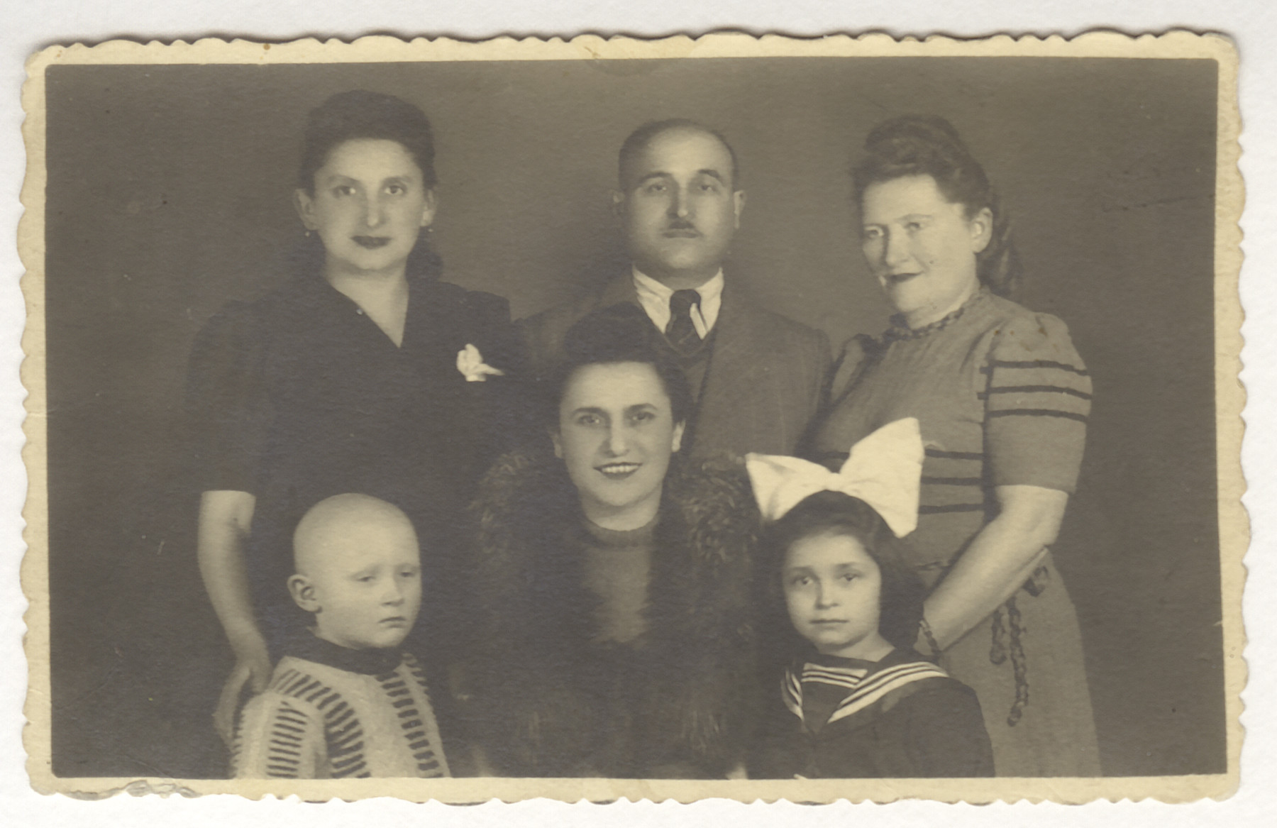 Studio portrait of surviivng members of the Jonisch family.  Top row: Cecia Jonisch, Sam Jonisch, Sophie Jonisch Bornstein.  Bottom row: Michael Bornstein, Hilda Jonisch and Ruth Jonisch.