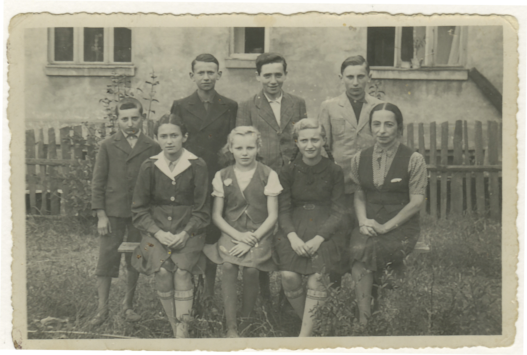 Group portrait of children in the clandestine school of the Zarki ghetto..    Among those pictured are standing lLeft to right Baum (the short boy standing far left), Marvin Zborowski, Steinbrecher, Bornstein (not related to the donor's family).  Bottom row seated left to right Varschwski, Granek, Sozia Naman (girl with braids) and the teacher Judicht.