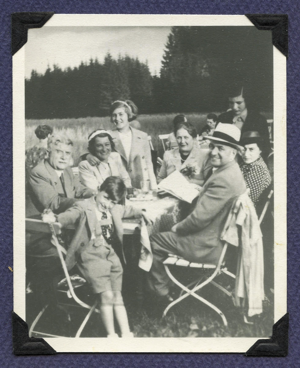 The Grunbaum family enjoys a picnic in prewar Czechoslovakia.  Michael Grunbaum is pictured front center.  His father Karel is seated to his right.  His mother Margaret is seated second from the left and his sister Marietta is standing next to her mother. Mrs Marta Kralova is seatd next to Karel wearing a hat and a dress with dots.  Dr. Jiri Kral on the left,