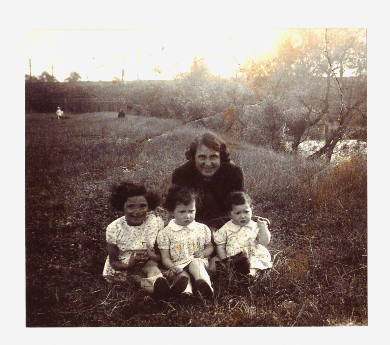 Dora Teitelbaum poses in a field with her three young daughters, Bertha, Malka and Bella.