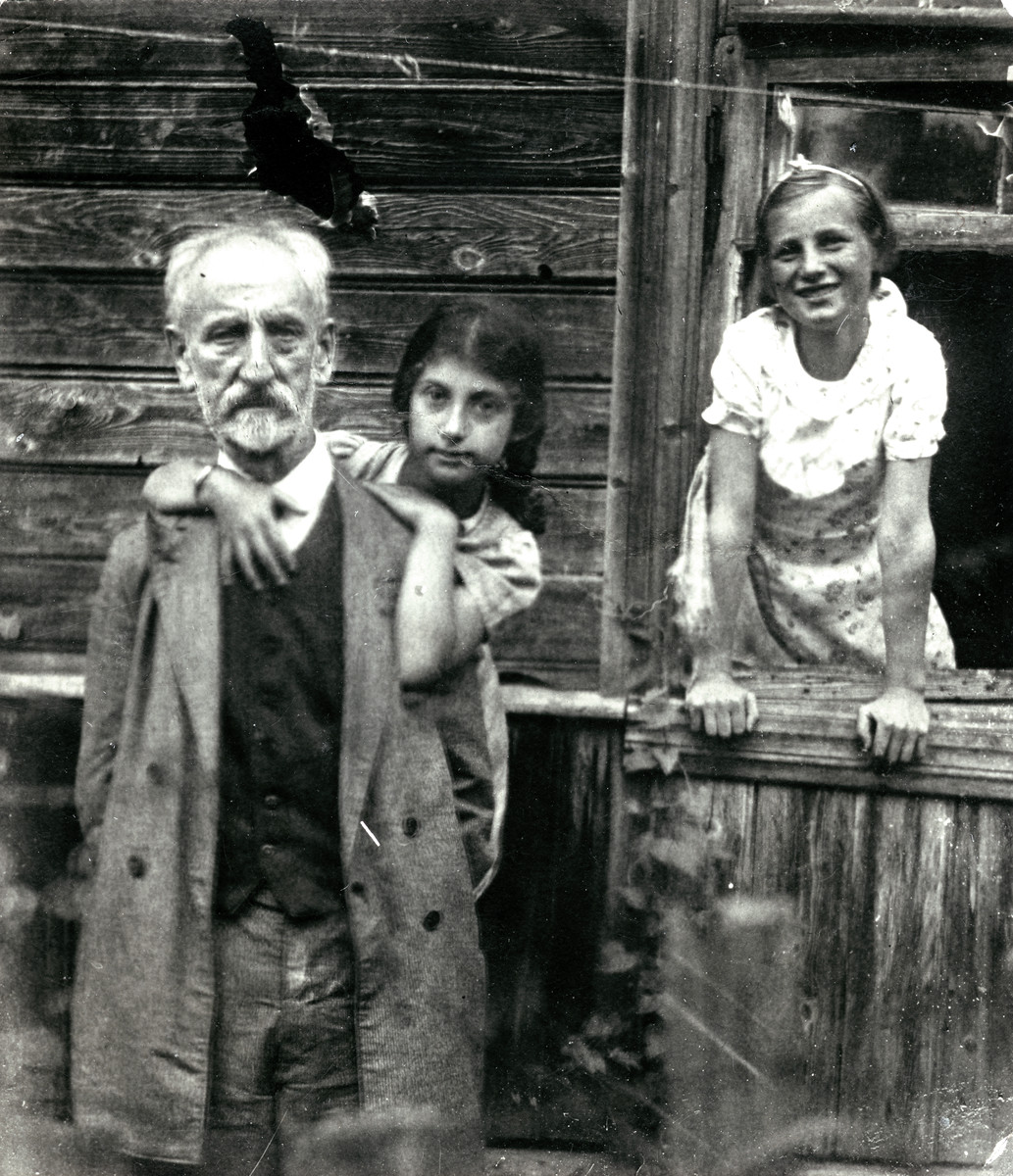 Tamara Magid leans against her grandfather David Magid at a summer resort, while a neighbor stands behind them.