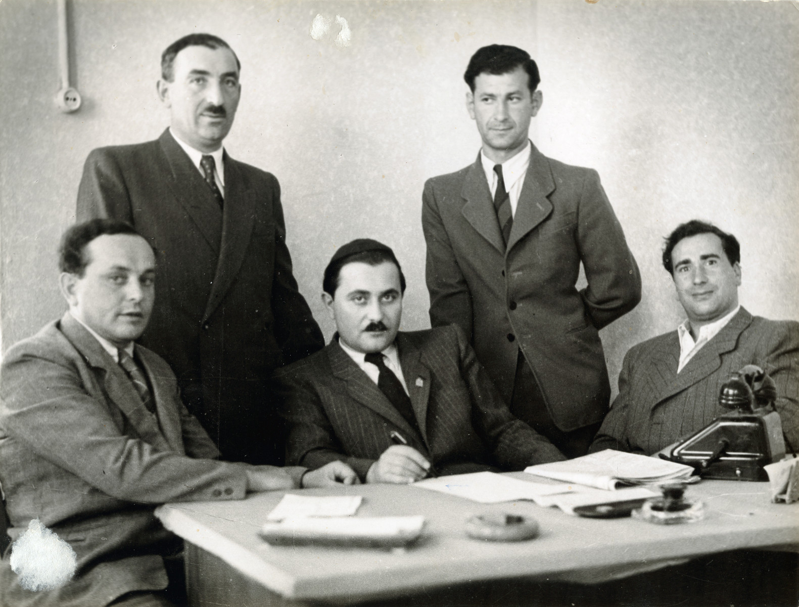 Group portrait of the leadership of the Pocking displaced persons camp.  Pictured seated left to right are Max Shmerler, Rabbi Yehuda Meisels, Yitzchak Golombeck.  R. Weinstein is standing right.