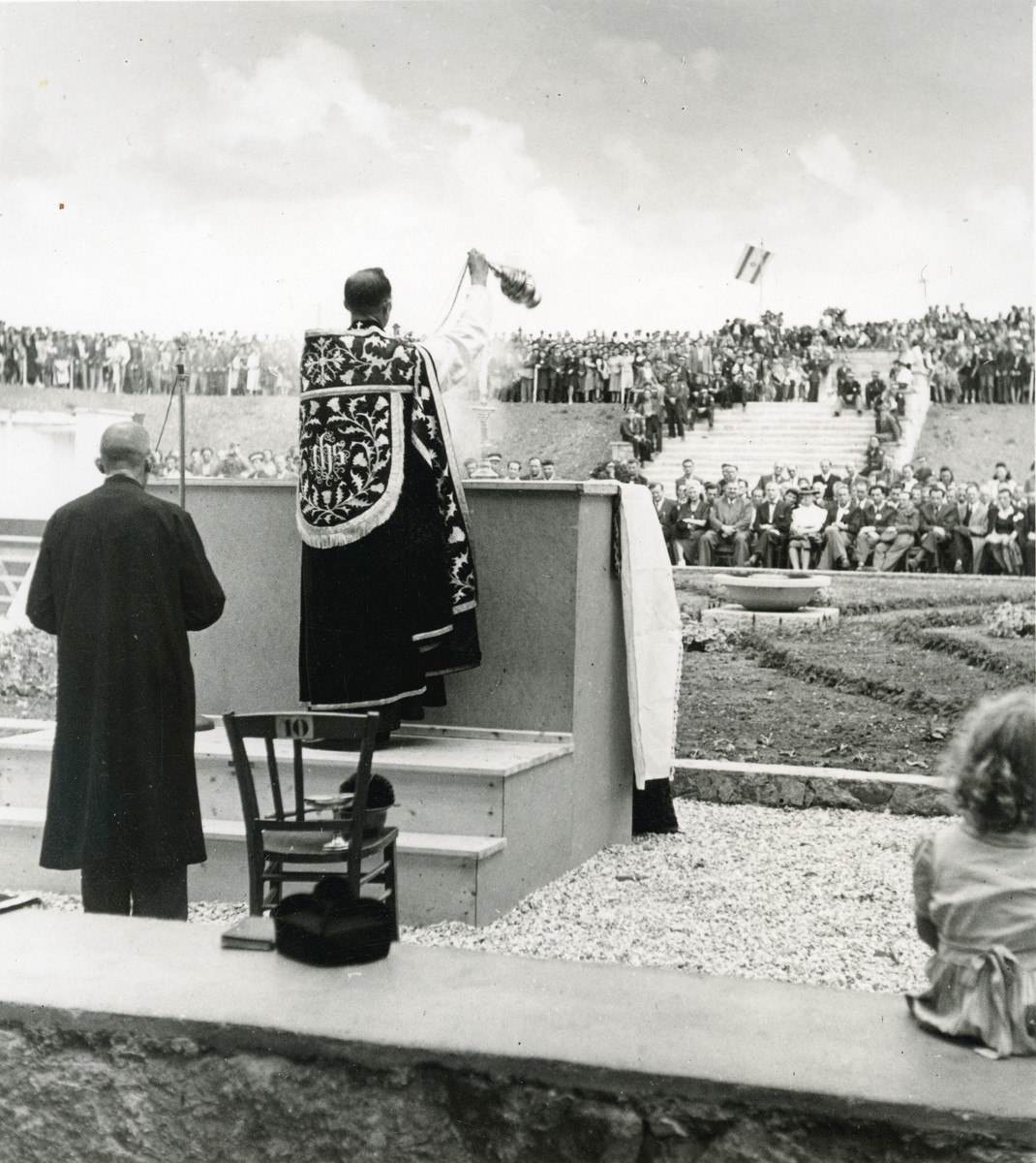 A priest leads prayers during the dedication of the monument to the victims of the Pocking concentration camp.