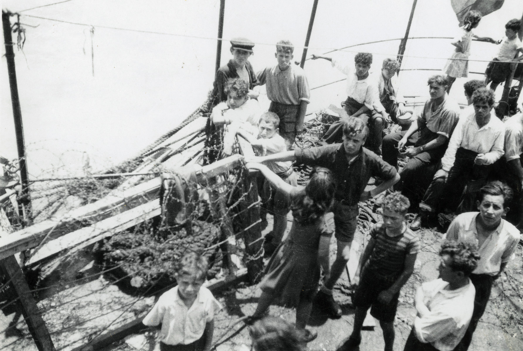 A group of teenagers stand on the deck of the Hatikvah while en route to Palestine.