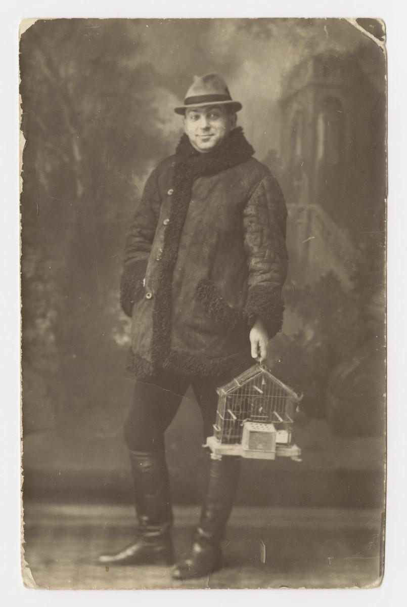 Portrait of Armin Schwalb holding a bird cage.
