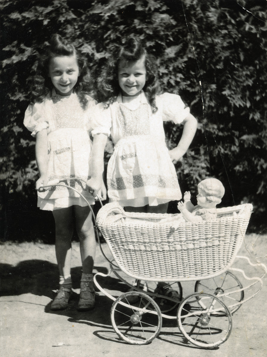 Miriam Meisels (right) poses with her sister Yehudit and a doll and carriage on her seventh birthday.