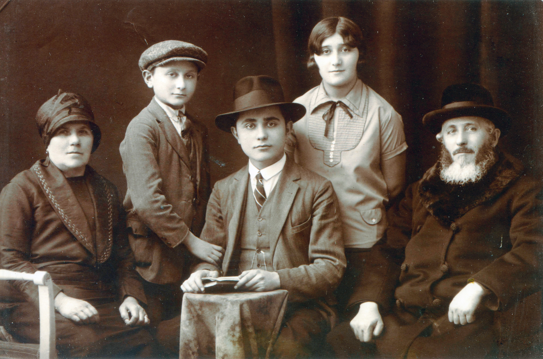 Studio portrait of the Meisels family.    Yehuda Lipot is seated in the center.  His parents Sara and Rabbi Shimon Chaim Meisels are on either side.  Standing behind are his brother Motchi and sister Margit.