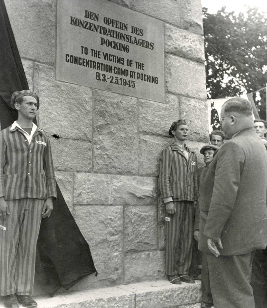 Two survivors wearing their concentration camp uniforms stand at attention in front of the newly dedicated monument to the victims of the Pocking concentration camp.  Philipp Auerbach stands in front paying his respects.