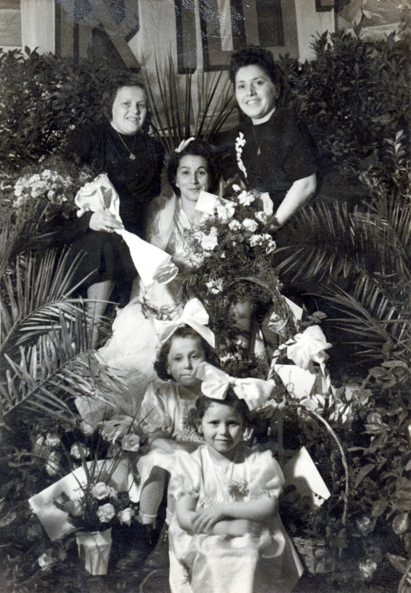 Women and girls attend the bride Chanka Smerler who is seated surrounded by flowers on her wedding day.  Miriam Meisels is pictured on the bottom and her sister Yehudit right abover her.  Standing in the back are Sara Meisels and Machuska Golombek.  Rabbi Meisels officiated at the wedding.