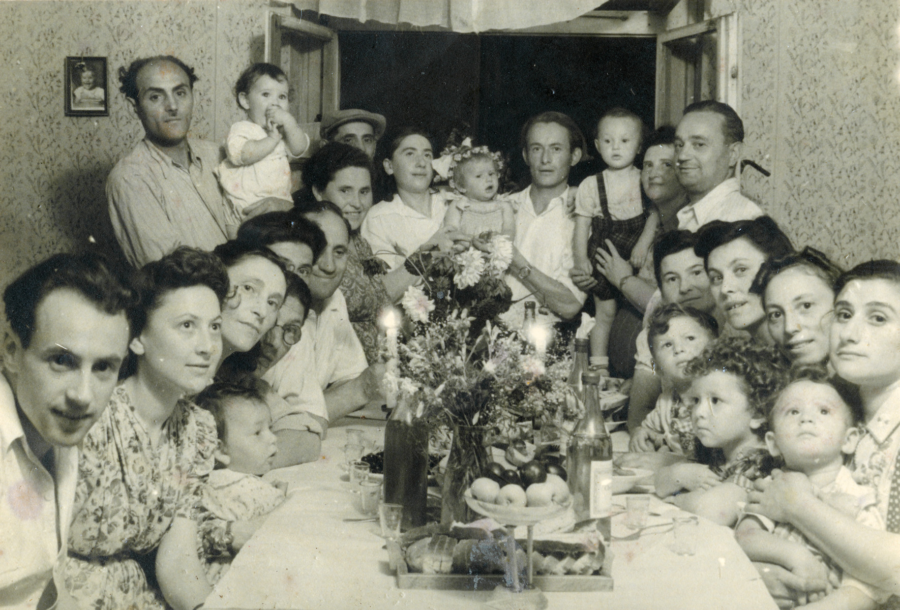 Hannah (child top right) and her parents Zvi and Ida Szklut attend a birthday party with lots of young toddlers [probably in the Bergen-Belsen displaced persons camp].