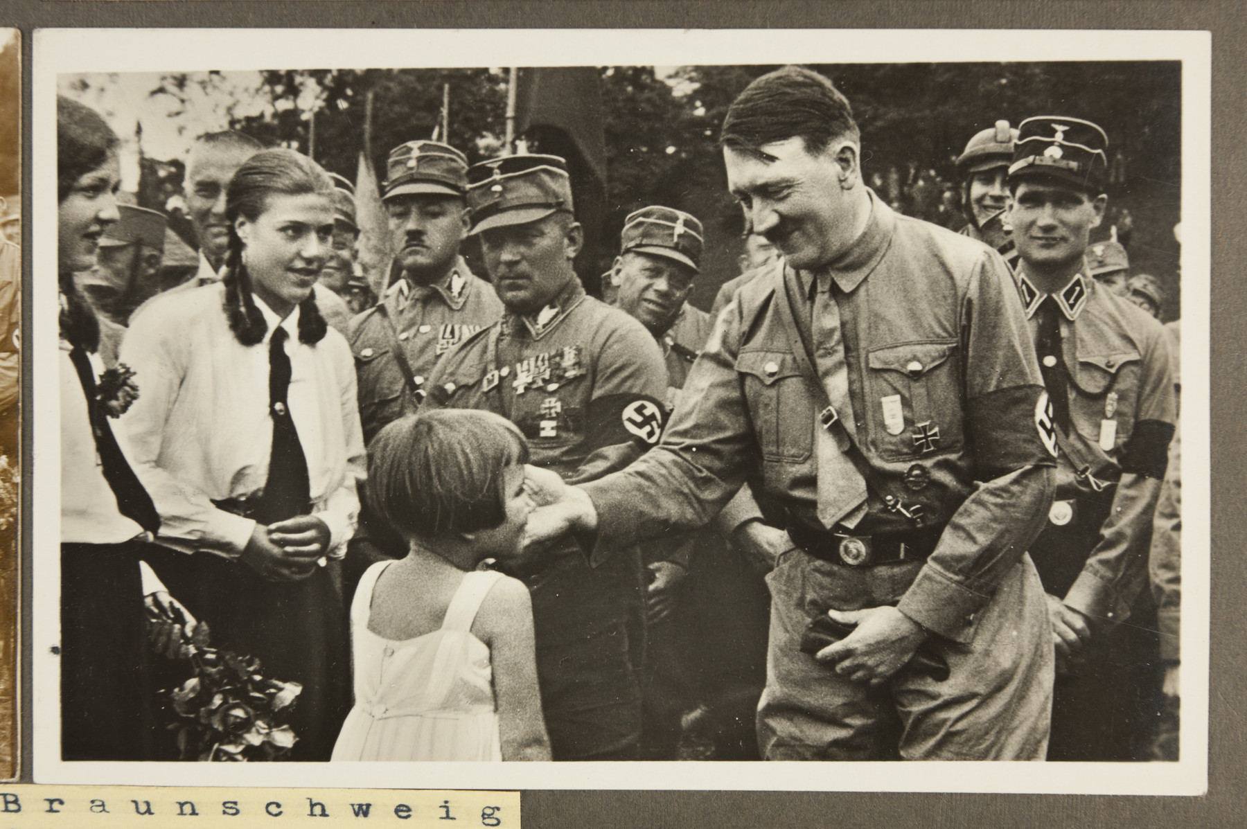 Adolf Hitler, surrounded by SA stormtroopers, greets girls during the annual Nazi Party congress in Braunschweig, Germany.   Also pictured are *(back, left to right) Wilhelm Frick (behind young woman with braids), Georg Von Detten, Manfred von Killinger, Adolf Hunleein, and Rudolf Hess.