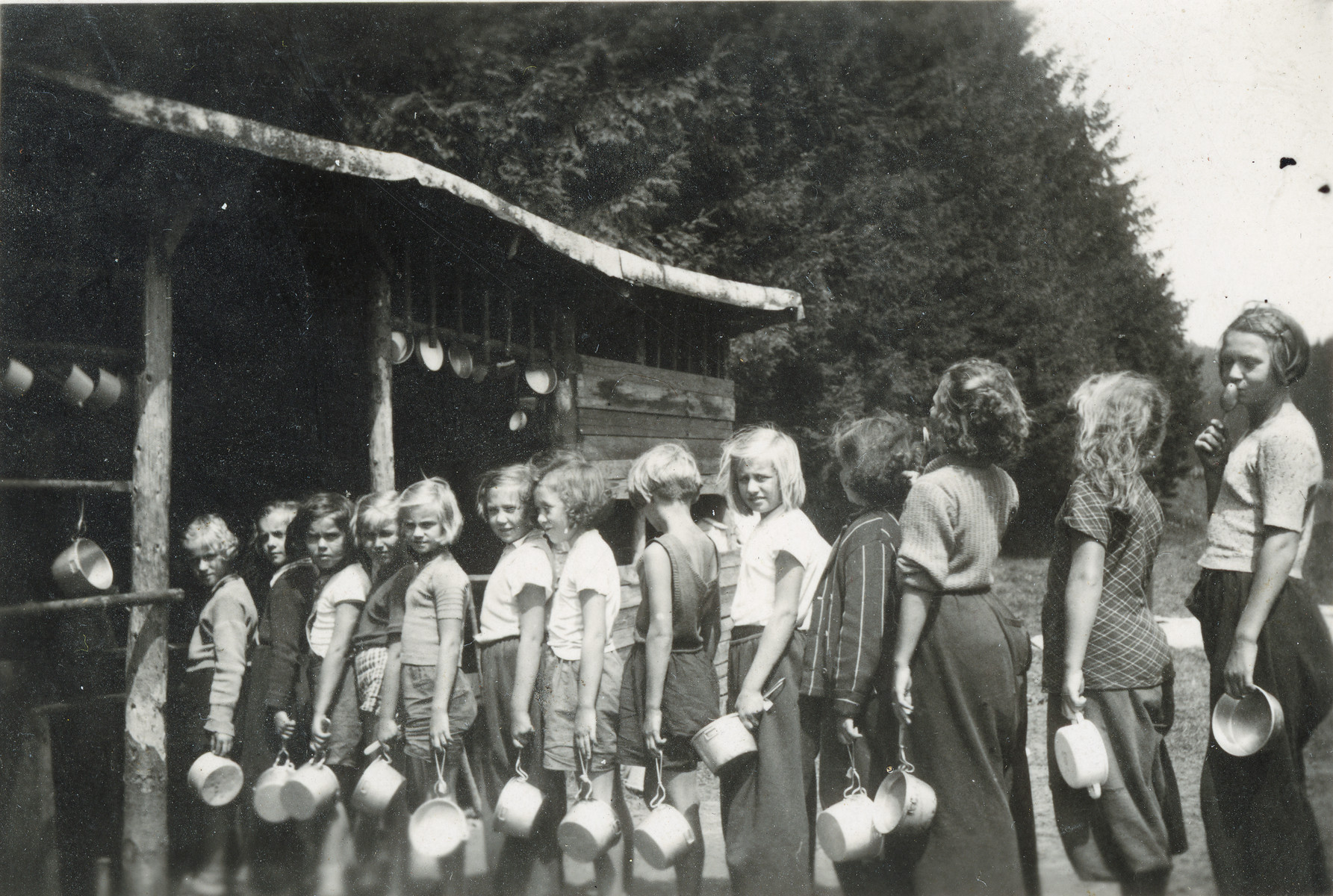 Young girls wait in line with their lunch pails in a summer camp in Czechoslovakia.