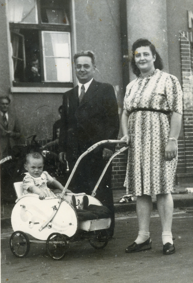Zvi and Ida Szklut pose with their infant daughter Hannah (inside a baby carriage) in front of a building in the Bergen-Belsen displaced persons camp.