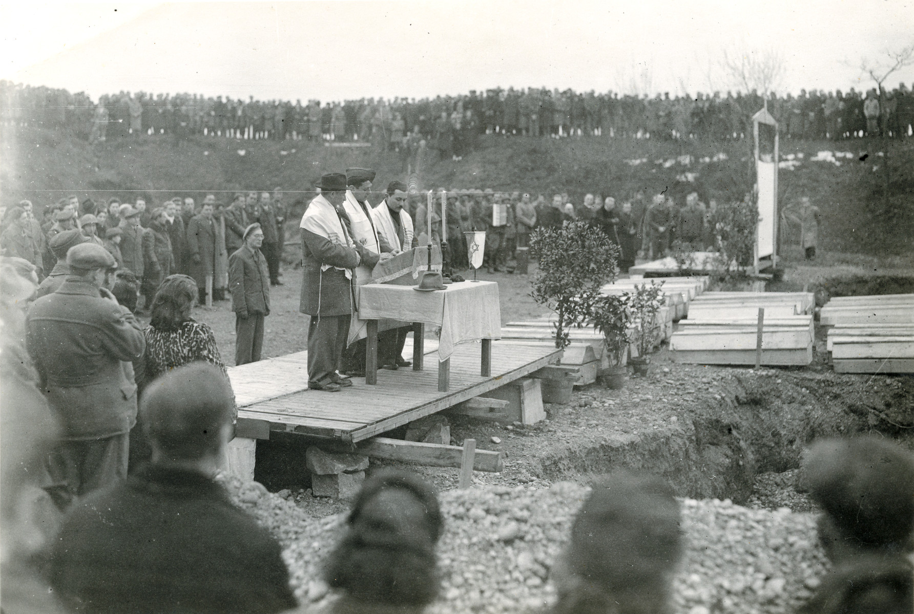 Rabbi Yehuda Lipot Meisels (right) presides over an exhumation and reburial service of the victims of the Pocking concentration camp.