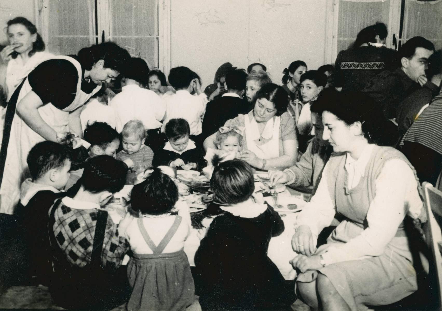 Female aid workers feed young children in the Bergen Belsen displaced persons camp.  Pictured are Elana Millman (the blond baby in the center wearing a sweater) and Zippy Orlin, the aid worker sitting in front.
