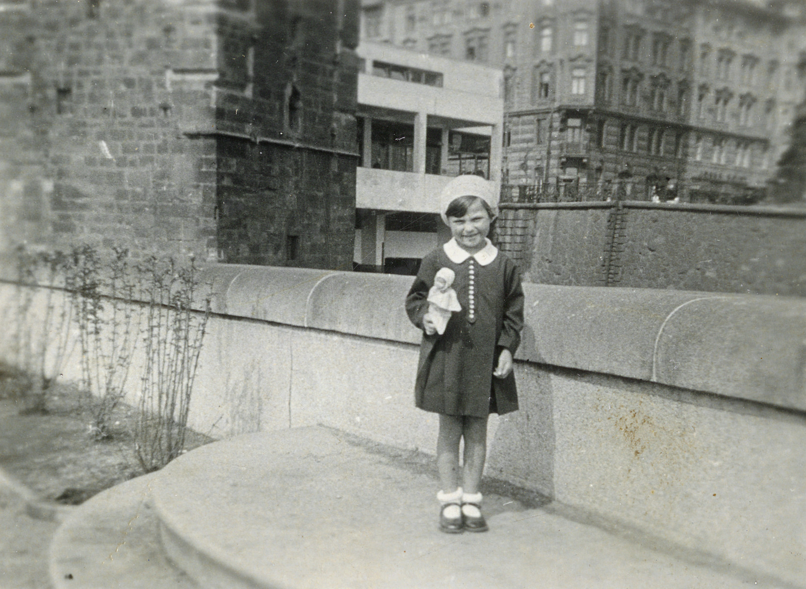 Hana Lustig poses on a sidewalk holding her doll.