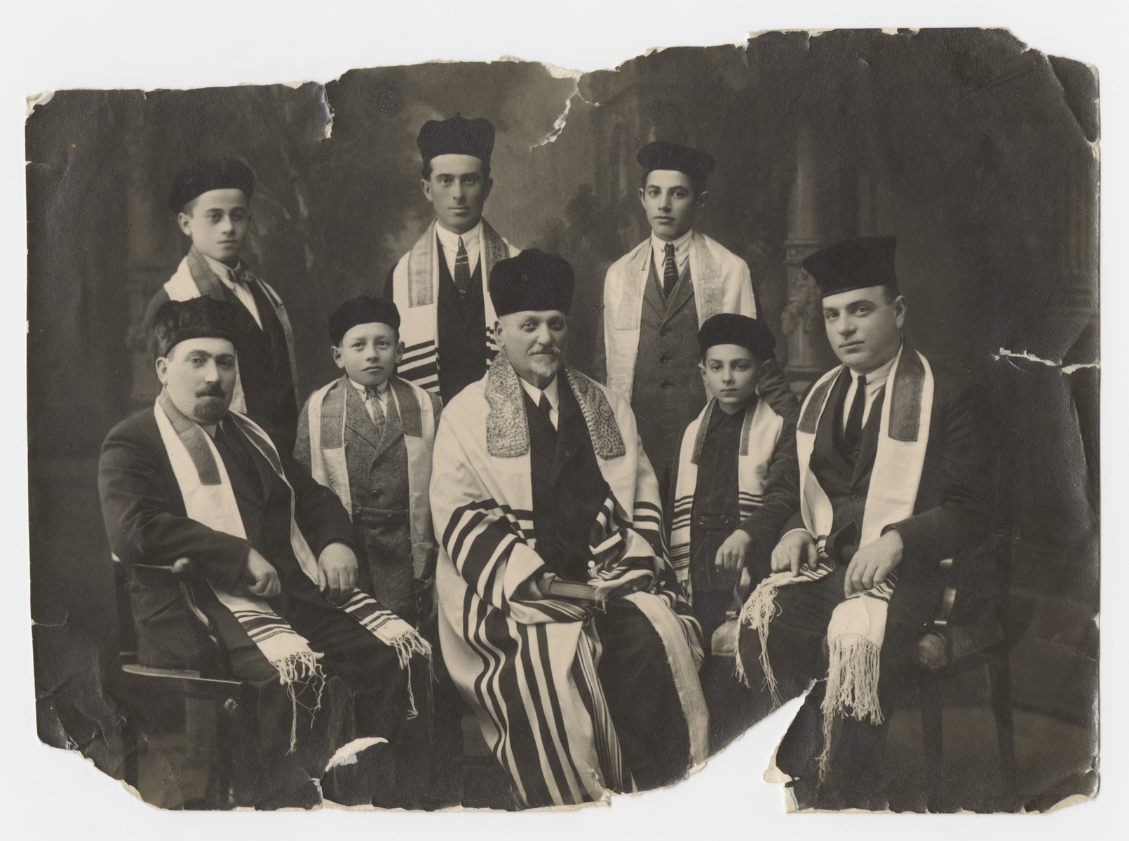 Group portrait of religious men clad in prayer shawls in Liptovsky Mikulas.  Rubin Schwalb is seated in the center, and his two young sons.are on either end.  Alexander is on the left and Armin is on the right.